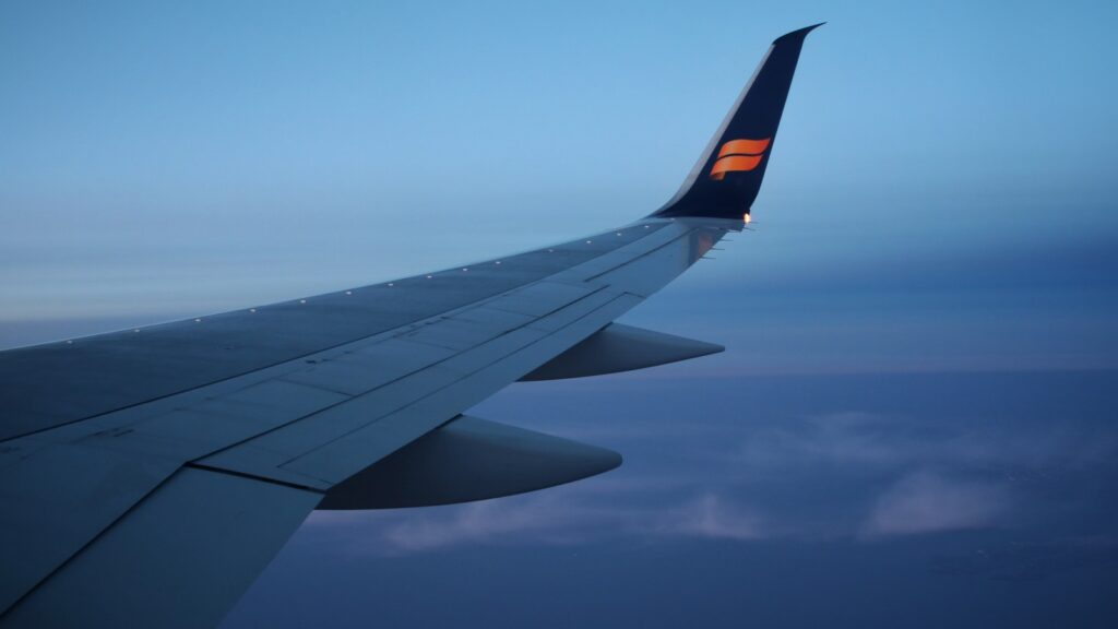 airplane wing under blue sky during daytime